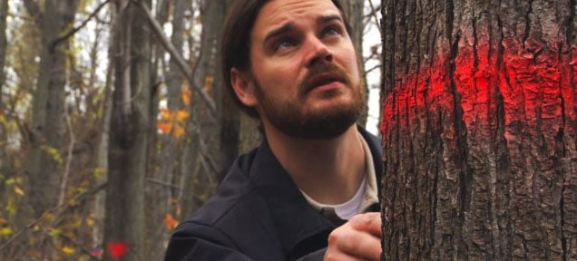 "USDA's Clint McFarland inspects trees infested with the Asian longhorned beetle, From ""Bugged: The Race to Eradicate the Asian Longhorned Beetle"" 20120, photo by Stavros Basis"
